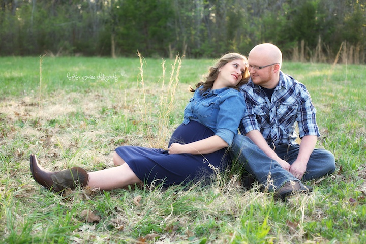 pregnant couple sitting in field