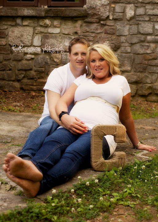 pregnant couple sitting with letter