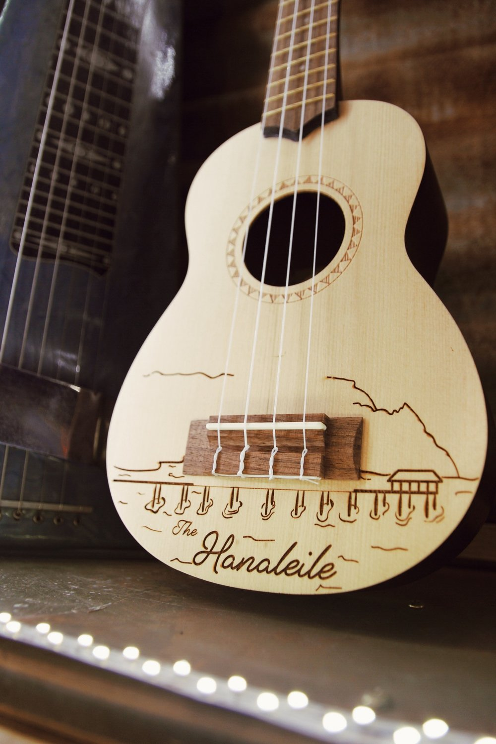 The Hanaleile - Our Hanaleile was designed by owner, Tora Smart, and is exclusive to Hanalei Strings. It depicts our historic Hanalei Pier and mountain range…
