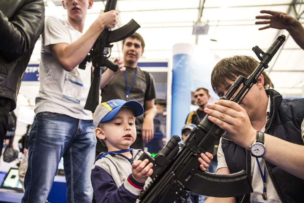 A boy tests AK assault rifles at Patriot congress and exhibition centre during an International military-technical forum