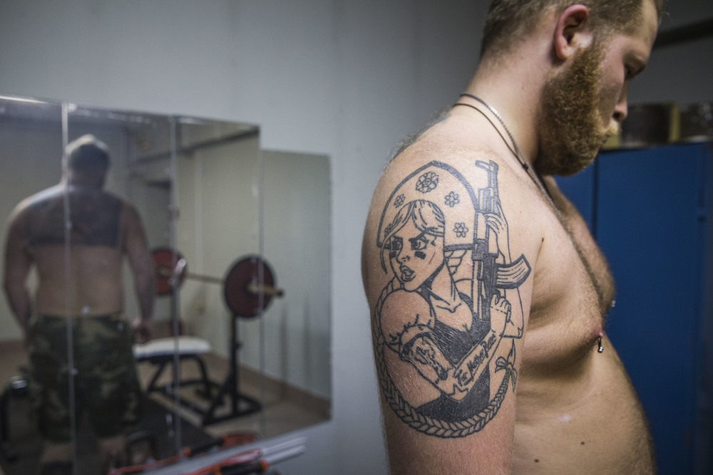 A tattoo showing a woman dressed in Russian national outfit holding AK assault rifle made by Moscow tattoo master is seen on Alexander, 25, while he exercises in a gym in Saint-Petersburg