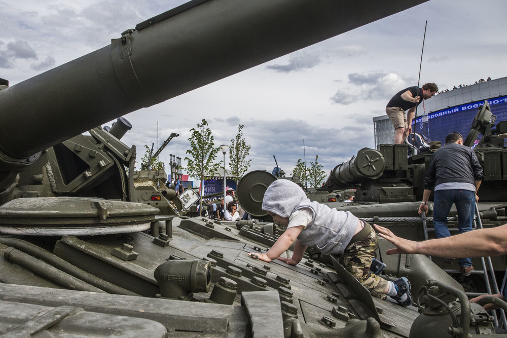 Both dressed in camouflage pants, father helps his infant son to explore a Russian army's tank that is shown at an exposition in Patriot park 40 kilometers from Moscow