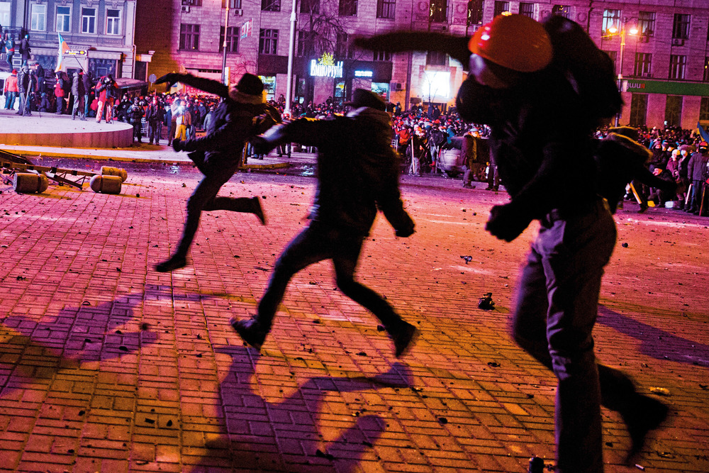 Protesters throw stones towards riot police forces