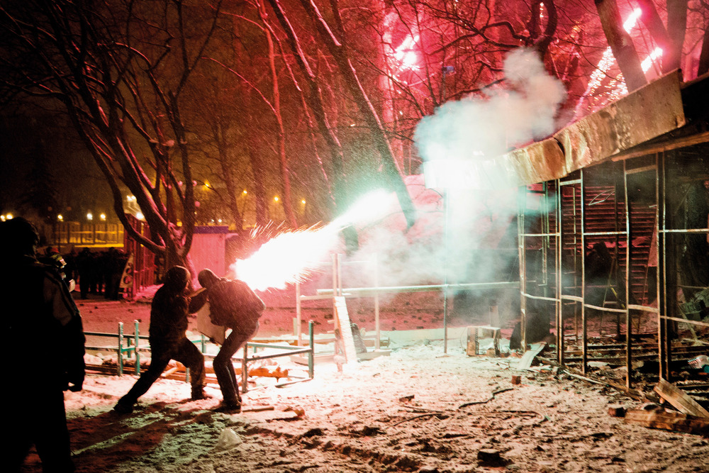 Protesters shoot with fireworks towards riot police forces