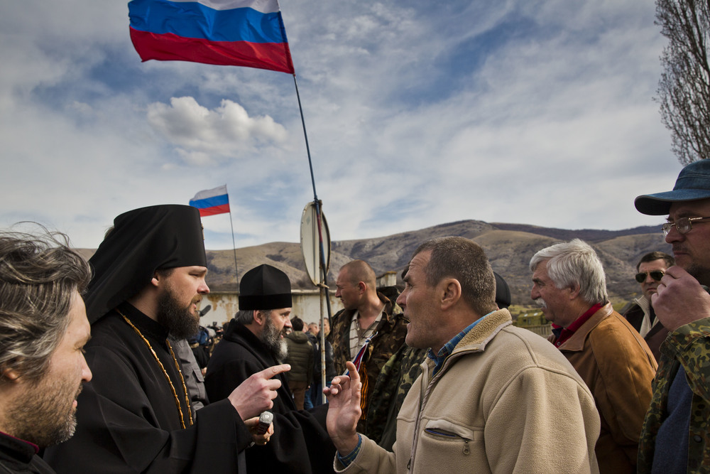 Pro-Russian militiamen are seen confronting a priest on his way to a church situated on Ukrainian military base