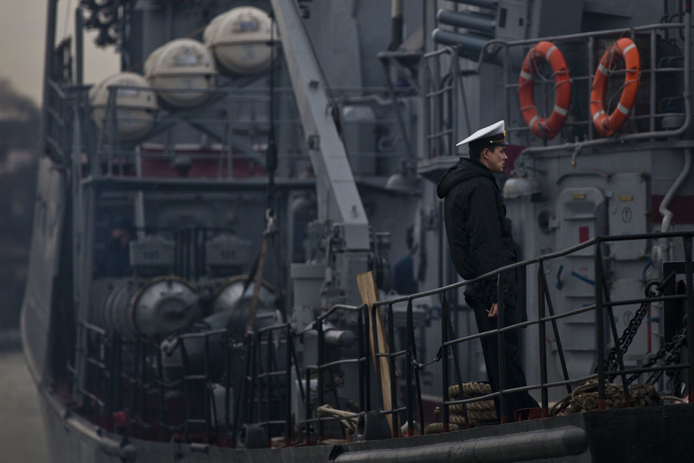 Ukrainian sailor is seen smocking on board of his vessel as it is blocked by Russian ships near Sevatopol