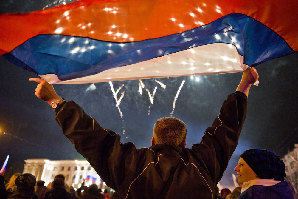 A man is seen holding Russian flag as Simferopol celebrates Crimea becoming a part of Russia