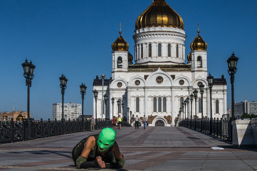 A member of Pussy Riot crawls past the Cathedral of Christ the Savior.  The band was arrested here following a performance in 2012.