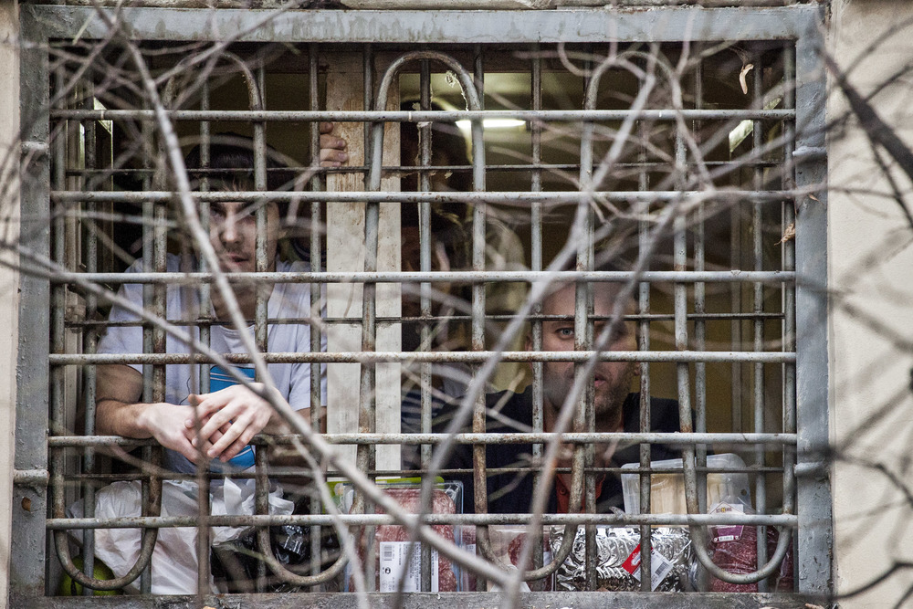 Alexey Navalny (right) is seen through the bars as he was arrested for an unlawful assembly in December 2011