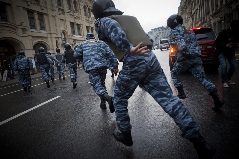 Riot police chases activists in Moscow downtown during 'Occupy Abay' protests in May 2012