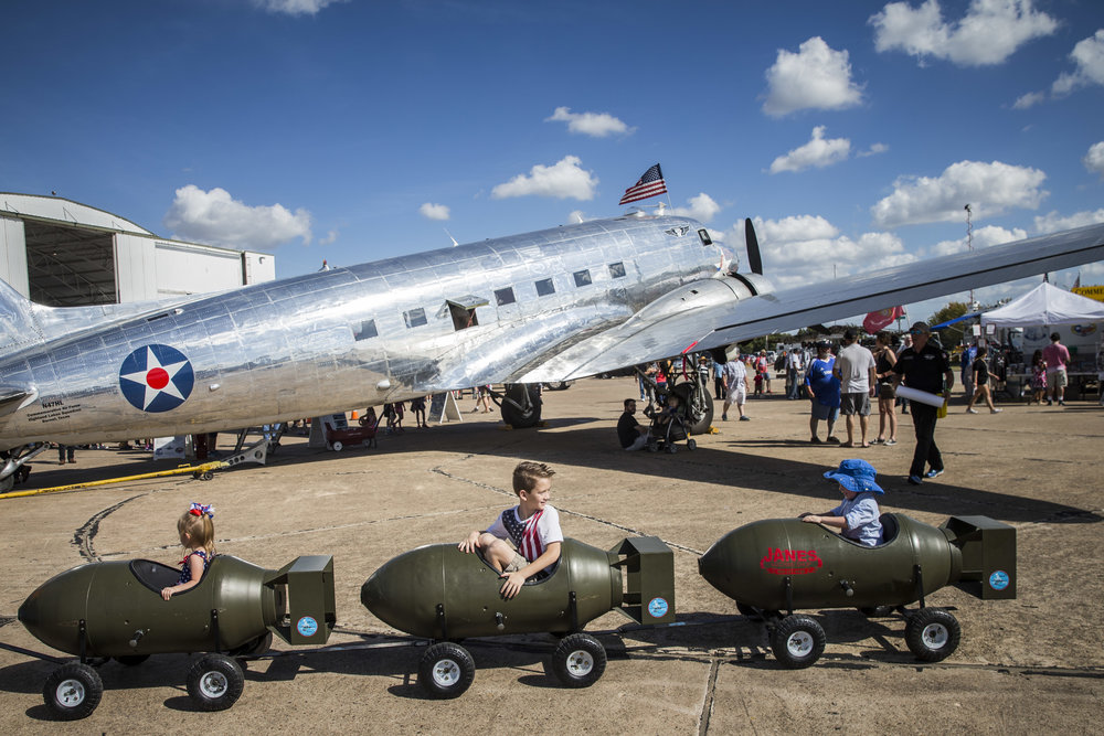 Children ride a bomb-shaped auto-train at an air show in Dallas, Texas
