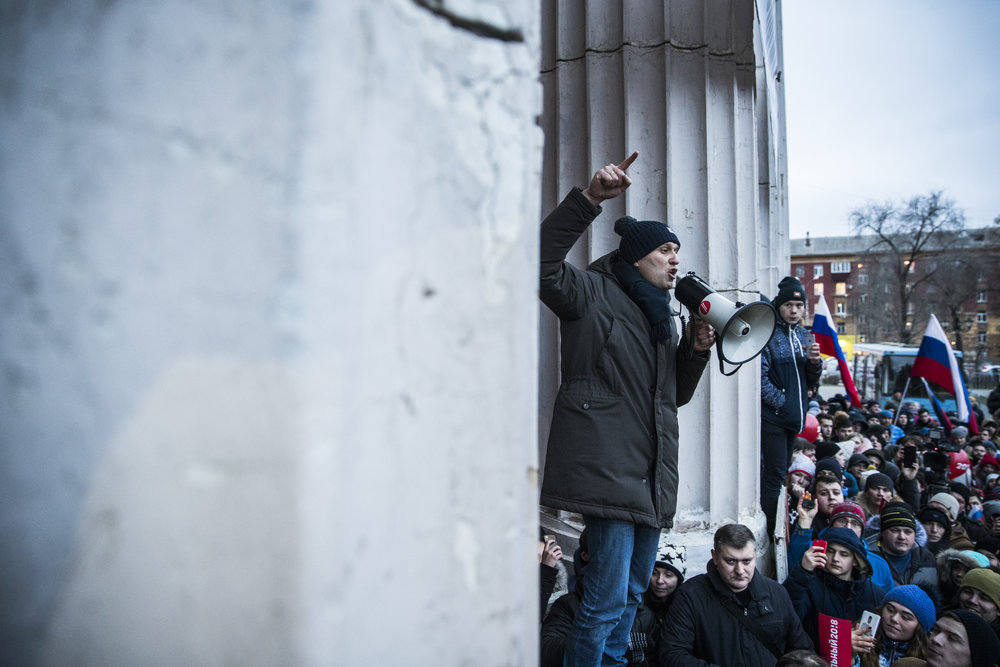 Alexey Navalny speaks into megaphone standing on a loudspeaker that was brought to the square in Samara to deafen his rally that was outlawed by the local government