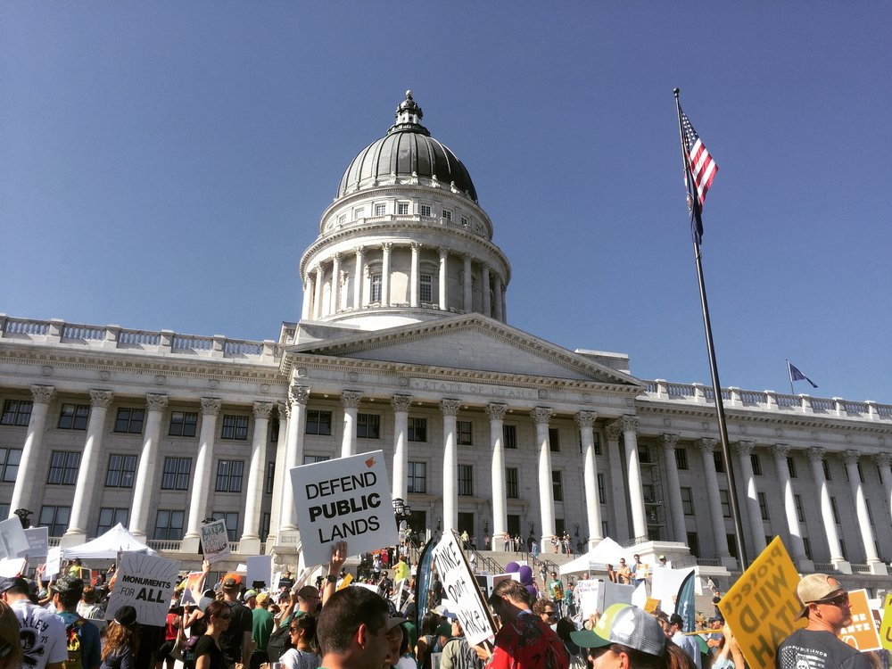 """The """"This Land is Our Land March for Public Lands"""" congregated in front of the Utah capitol in Salt Lake City on July 27 in conjunction with the last Outdoor Retailer Summer Market trade show to be hosted by the city. OR recently agreed to move the trade show to Denver starting next year in response to Utah lawmakers' continued efforts to rescind Bears Ears and Grand Staircase Escalante National Monuments. [Photo] Emma Murray"""
