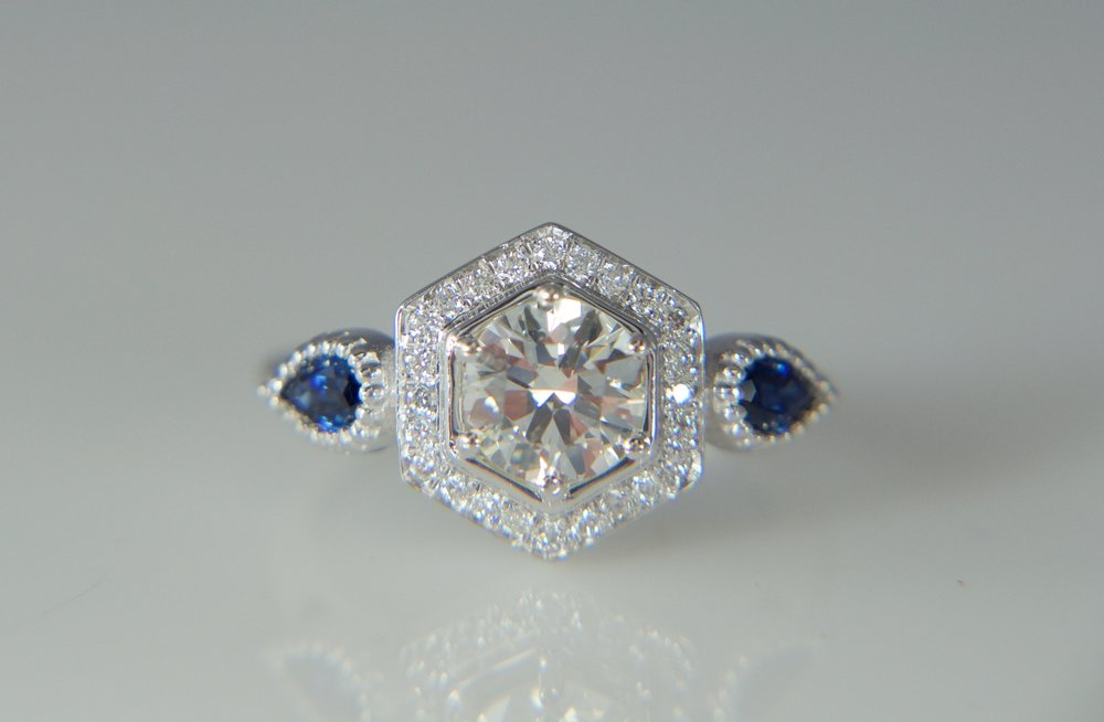Round diamond halo engagement ring with sapphires