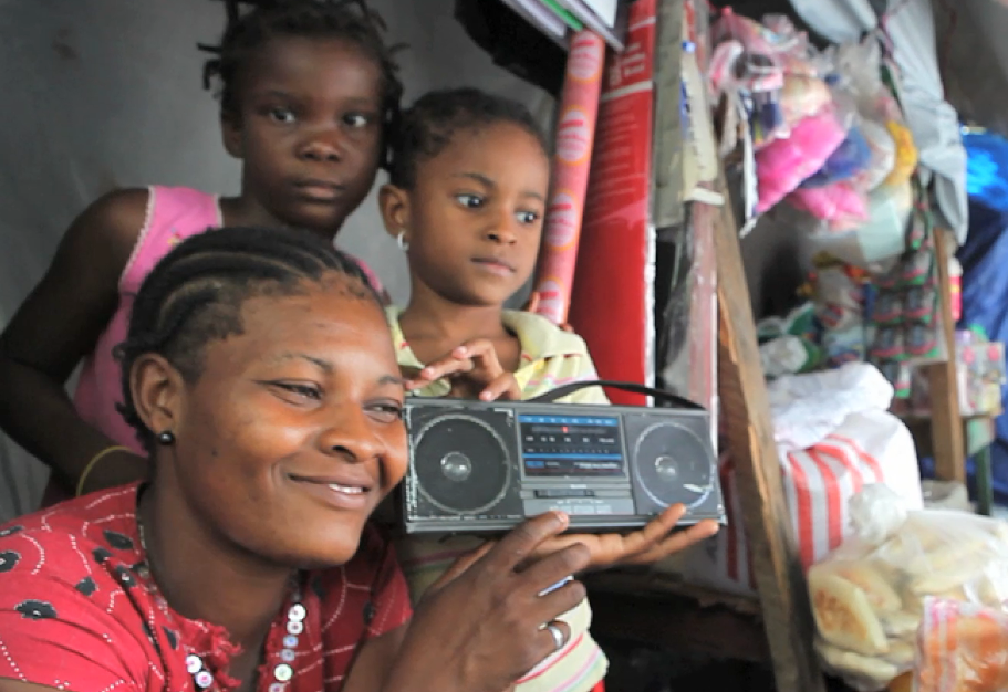 A family gets health and other vital information from a radio program after the 2010 earthquake in Haiti.