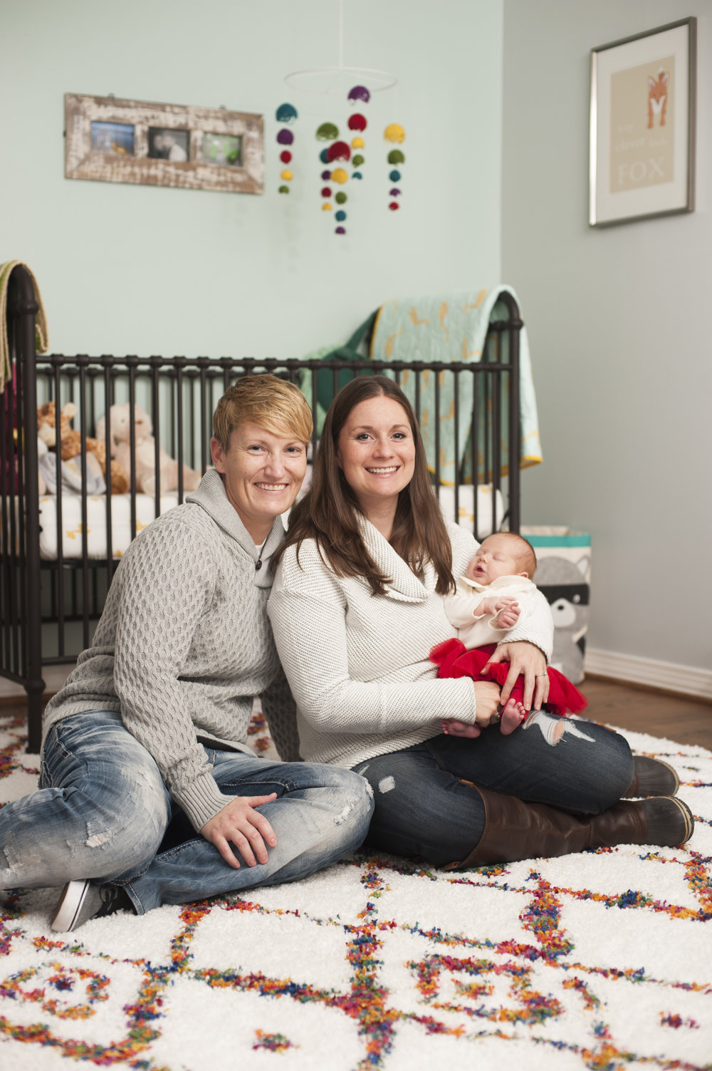Two mothers seated with newborn in nursery.