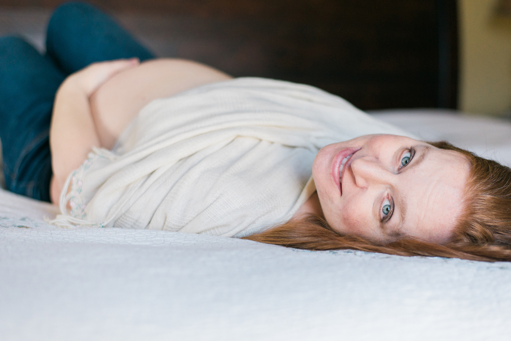 Buckinghamshire Indoor Maternity session shows intimate moment of mom holding her pregnant belly while laying on her bed.
