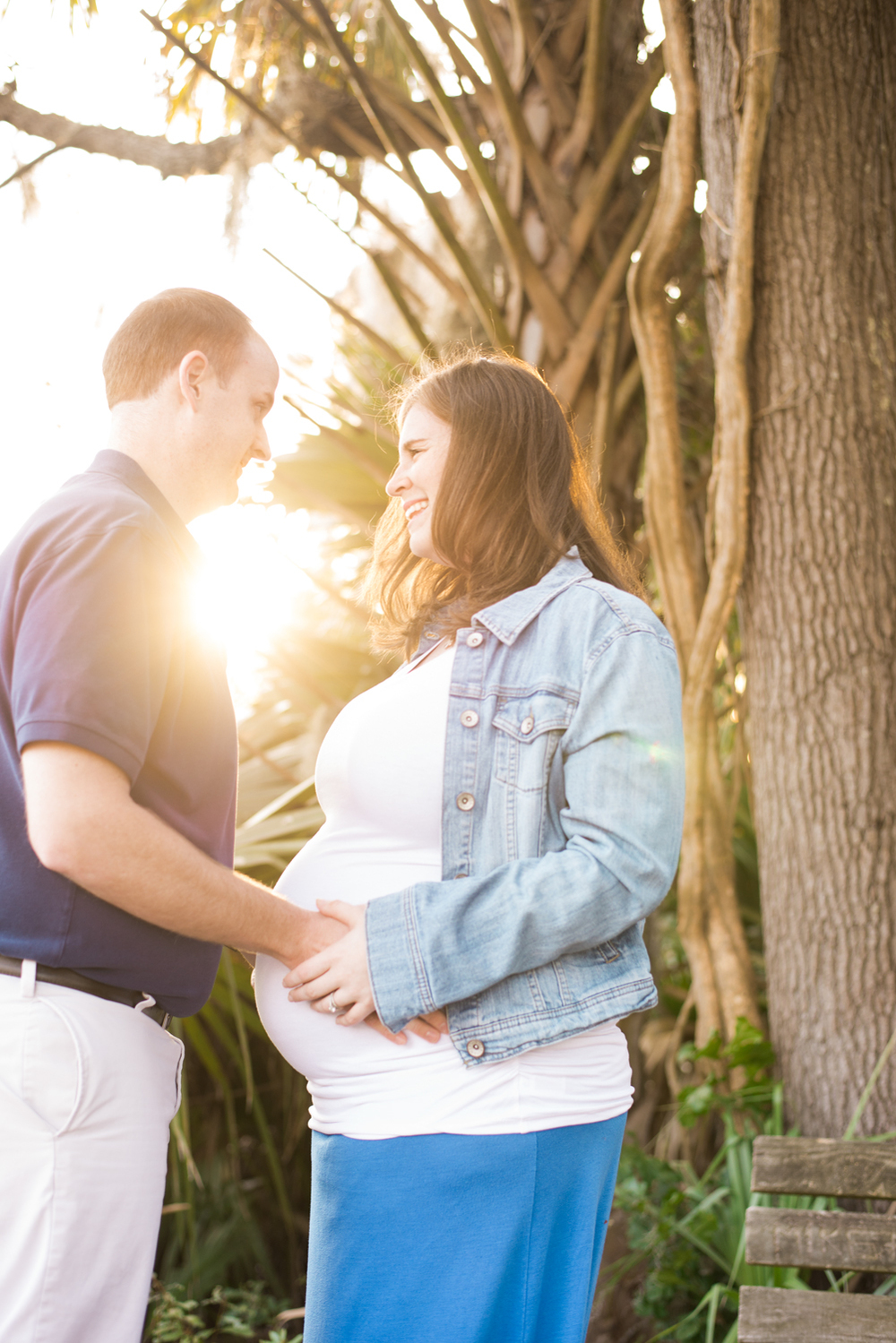 Bicester couple embrace mum's pregnant belly during sunset.