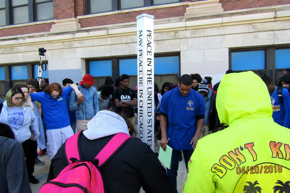"Tilden Career Community Academy students gather around the school's ""peace pole"" April 20 for the National School Walkout. Photo by Samuel Davis."