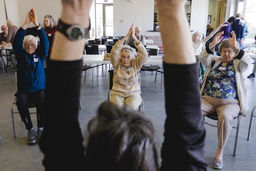 Marcia Cozzi, center, stretches with other members of the Chicago Hyde Park Village during their bi-monthly drop-in where seniors can exercise and interact with other community members over lunch. The village was formed to help members remain active and involved in their community.