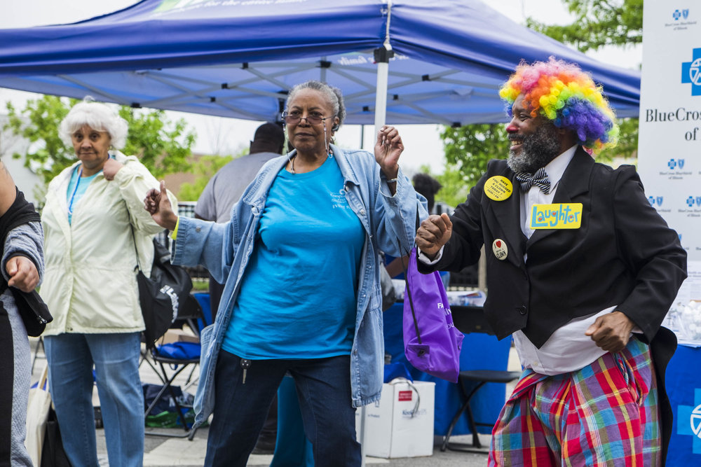 "Antonio Sanders, a member of the Senior Clown Troupe, dances with older adults during the Englewood Exclusively Us Senior's Day Celebration. Sanders and the Senior Clown Troupe performs for older adults in nursing homes and retirement centers. ""Clowning means to me being fun, keeping positive feeling, making someone that is sad, make them happy. Talk about positive things when they talk about sad things, so you make a sad situation to a positive situation. I really love that because it's my whole life and I grew up clowning,"" said Sanders, who started clowning when he was 17 years old and worked for the Ringling Brothers and Barnum Bailey Circus for a year and a half. As he grows older, clowning has become a more important part of his life. ""Clowning is not always being in the circus all the time. It's everyday life."""