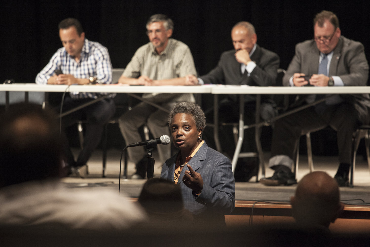 Lori Lightfoot speaking at a microphone in front of an audience
