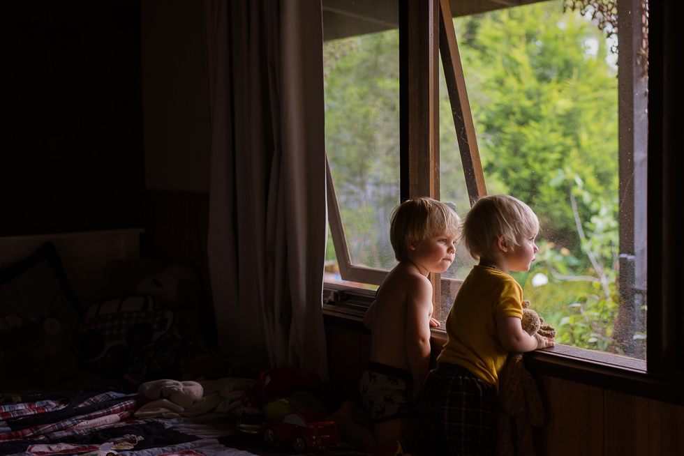 two_brothers_looking_out_a_bedroom_window_together_in_beautiful_light