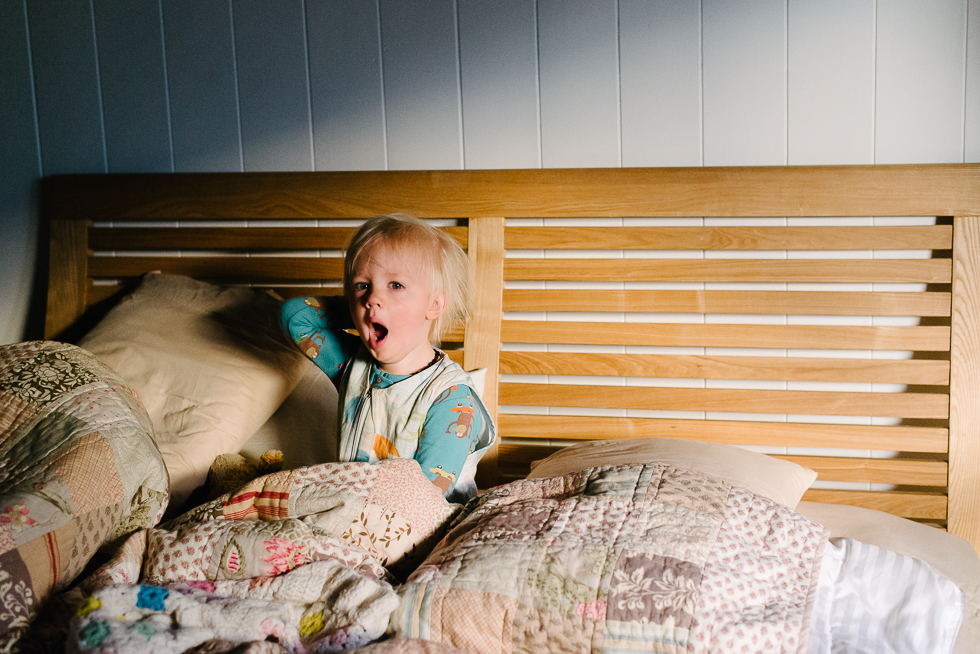a_boy_in_a_sleeping_bag_yawning_in_bed_in_morning_light