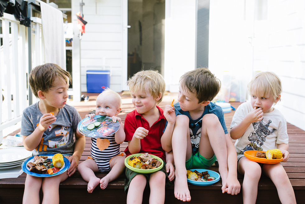 children+eating+dinner+outside+with+baby+eating+her+plate+in+melbourne+summer+Jenny+rusby+photography+melbourne+documentary+photographer