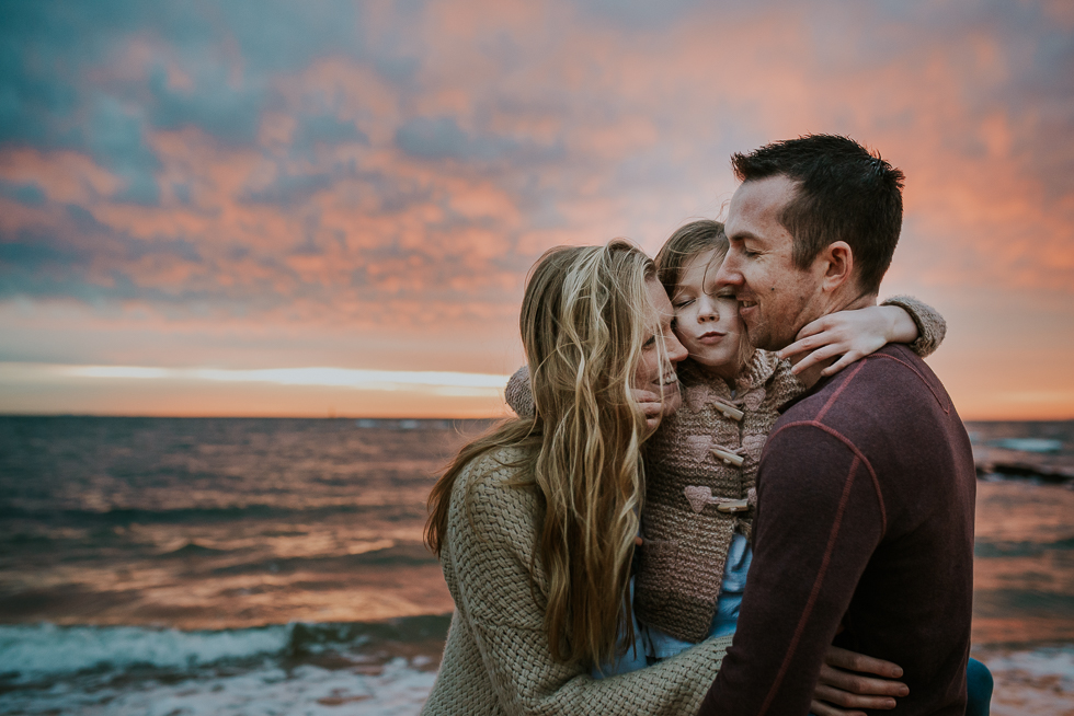 family+cuddling+at+sunset+at+the+beach+with+pink+clouds+in+melbourne+Jenny+rusby+photography+melbourne+family+photography