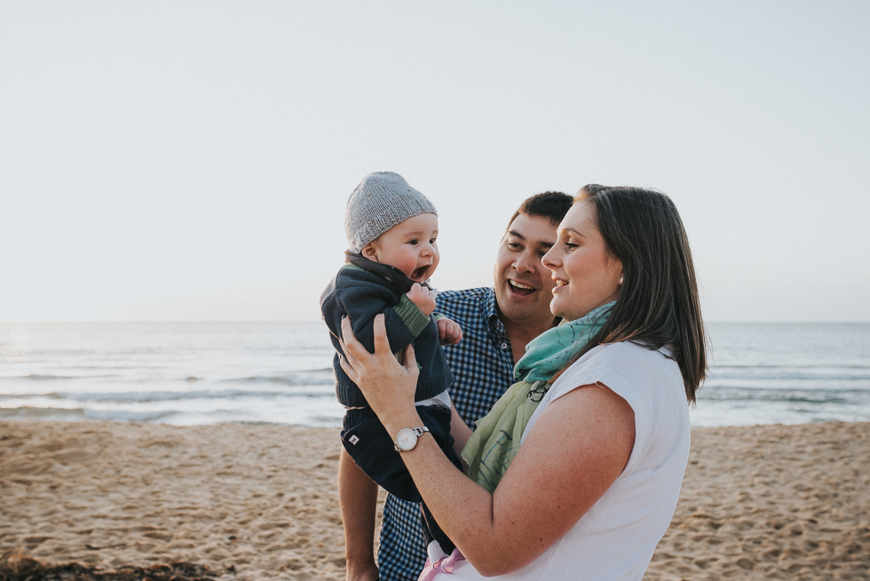 mum+and+dad+holding+smiling+baby+at+beach+melbourne+family+photographer+lifestyle+Jenny+rusby+photography