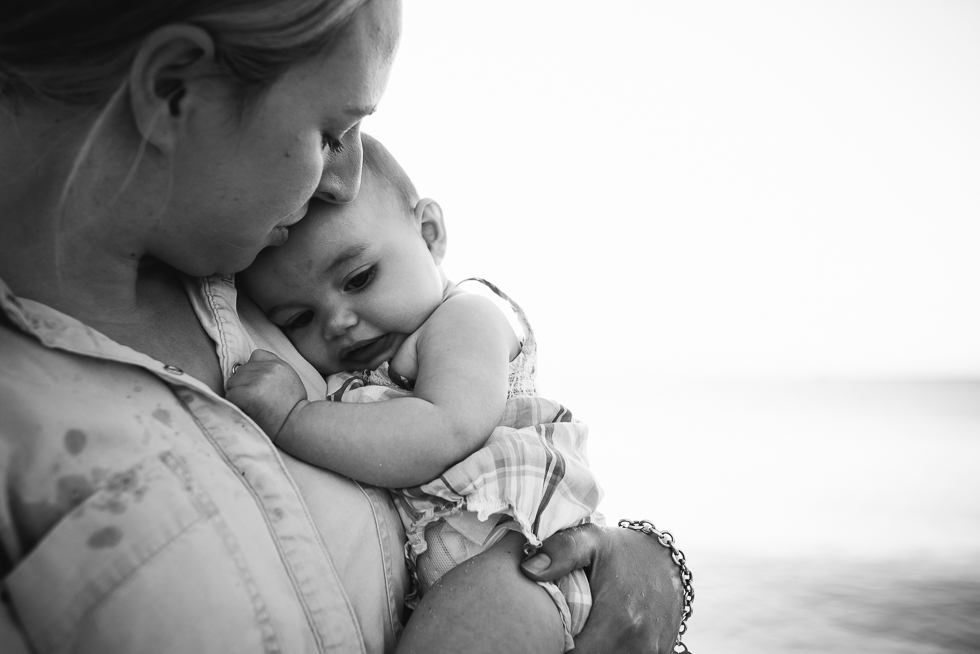 mother+holding+baby+in+loving+embrace+in+a+black+and+white+photo+at+the+beach+in+melbourne+Jenny+rusby+photography+melbourne+baby+photographer
