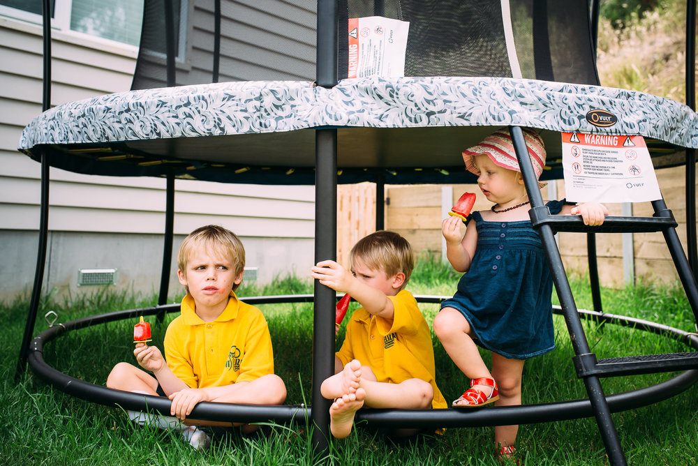 melbourne family photographer  mornington peninsula photographer  family photographer  family photography  family   siblings eating ice creams   kids eating ice creams under a trampoline