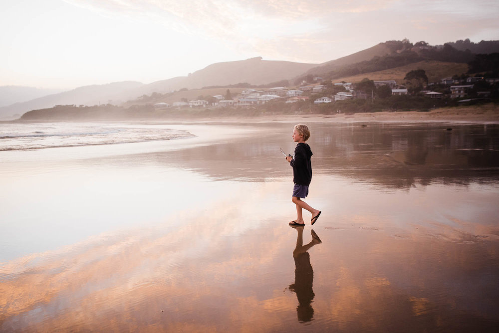 boy+at+the+beach+at+sunset+reflection+pink+sky+clouds+water+melbourne+family+photographer+Jenny+rusby+photography