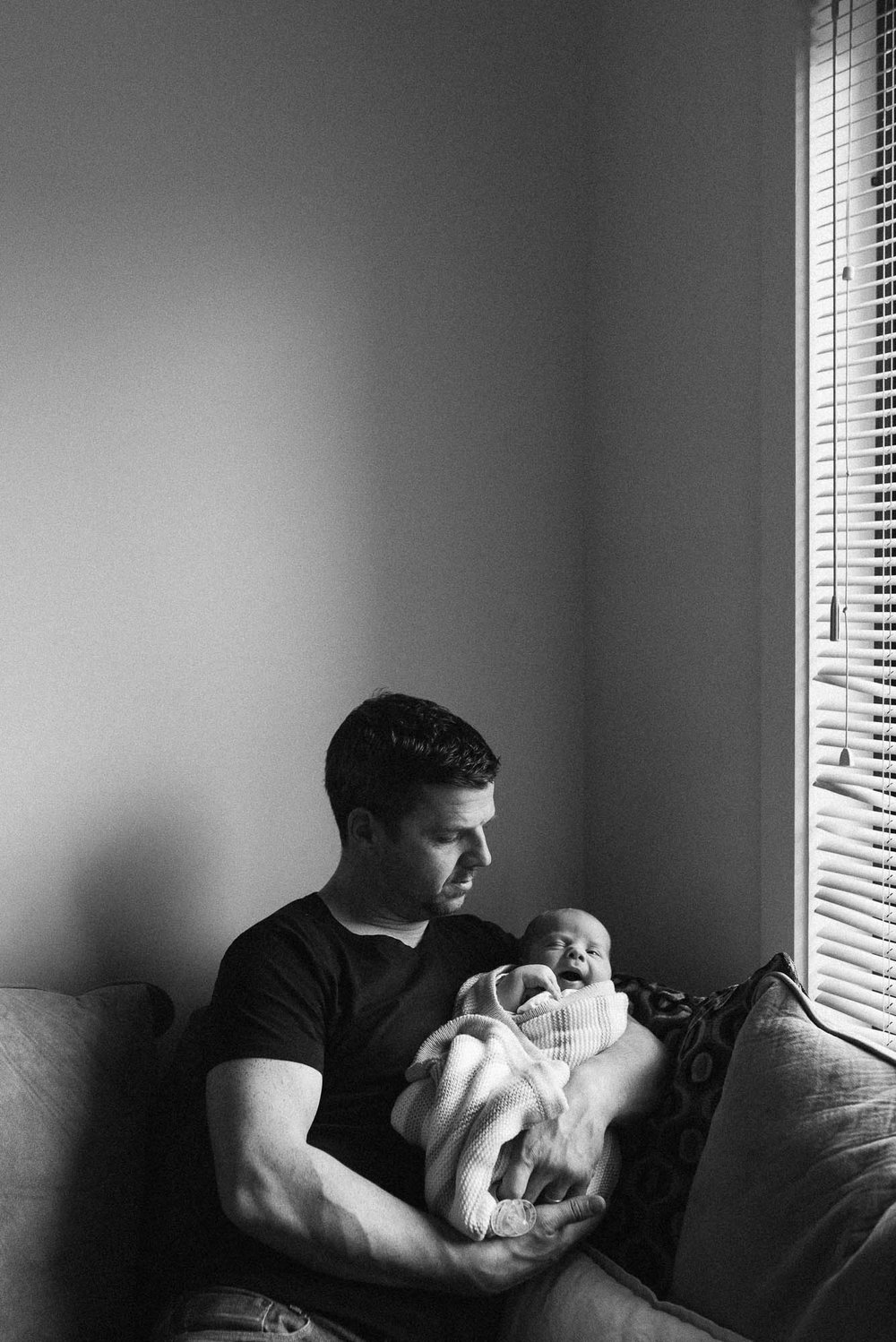 dad holding his newborn baby at an in-home newborn photo session