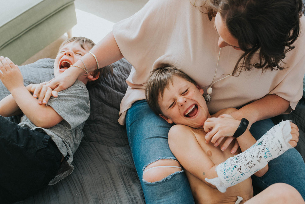 boys laughing while being tickled by their mum