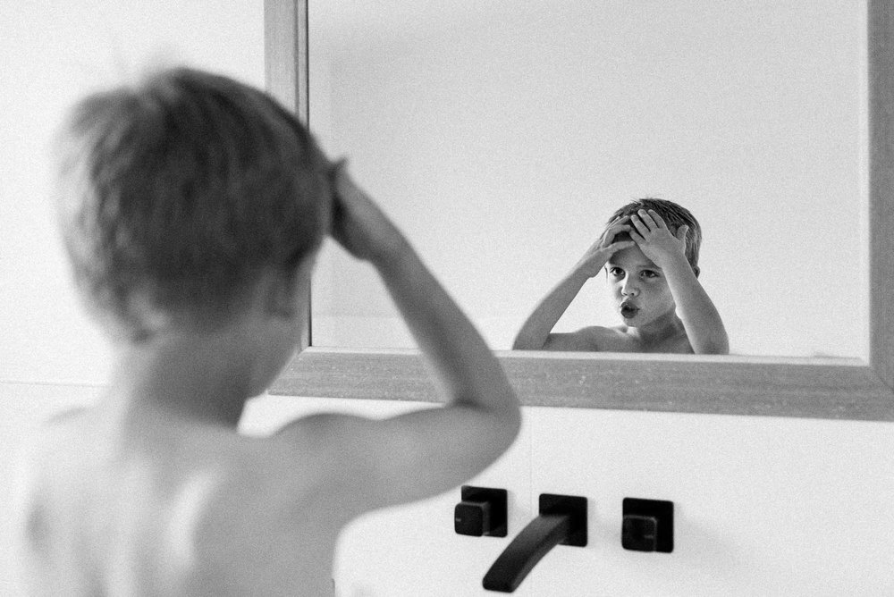 boy-doing-his-hair-in-front-of-the-bathroom-mirror-in-black-and-white