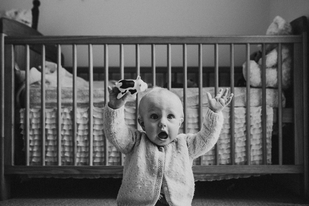 baby-sitting-with-arms-up-in-the-air-in-front-of-cot-in-black-and-white