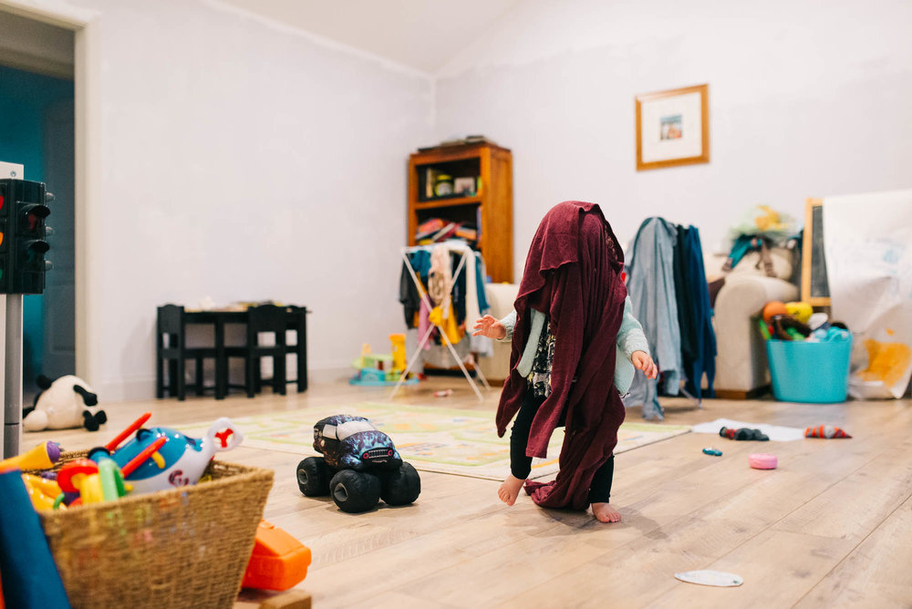 toddler-with-laundry-over-her-head-in-playroom