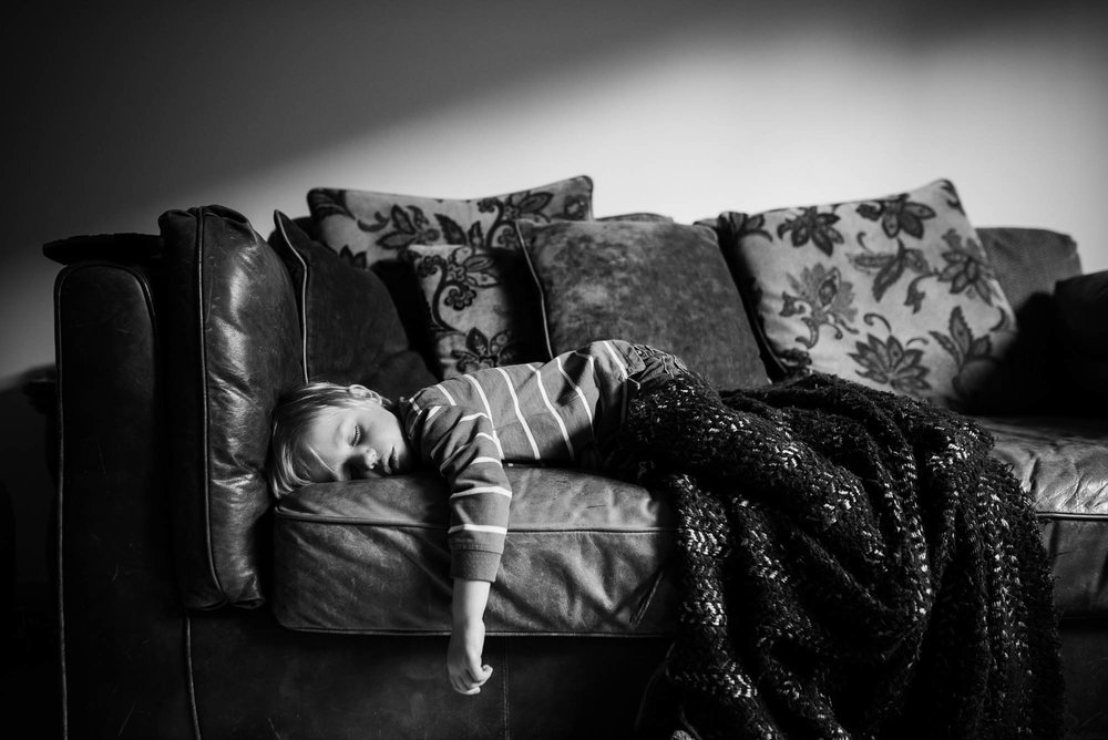 boy-asleep-on-the-sofa-with-a-blanket-in-black-and-white