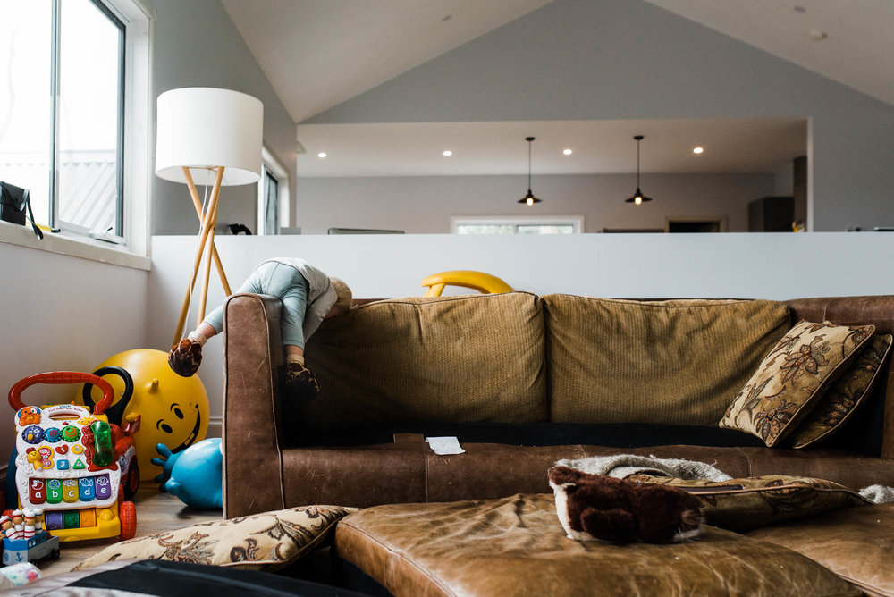 toddler-climbing-on-sofa-with-cushions-all-over-the-floor