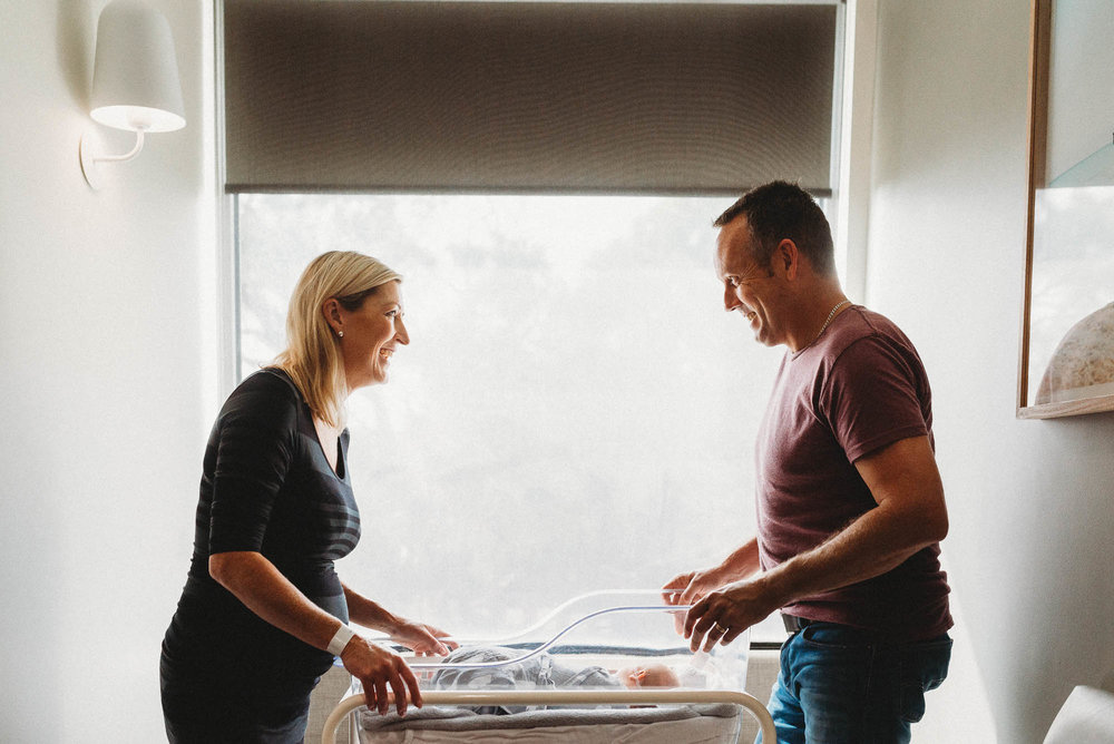 parents-looking-at-newborn-in-bassinet-at-hospital-melbourne