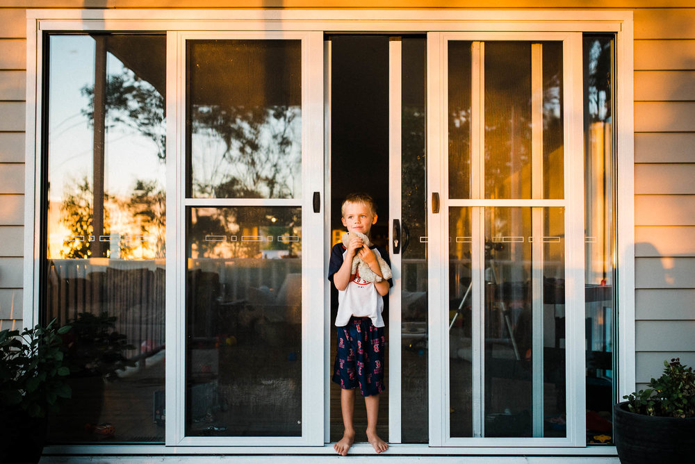 melbourne_family_photographer_boy_in_doorframe_at_sunrise.jpg