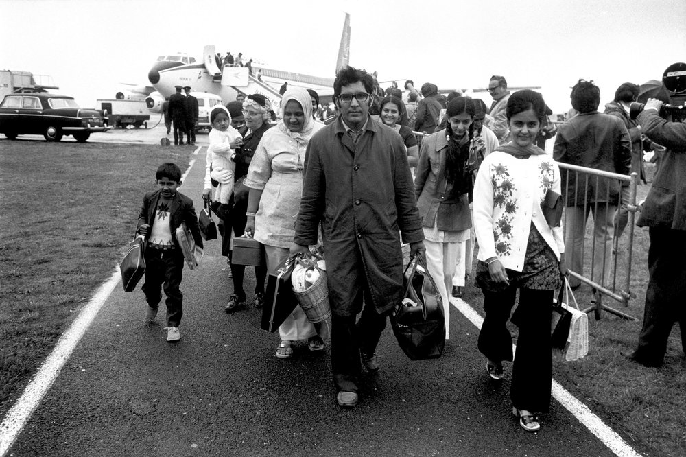 - In 1972 Idi Amin, the President of Uganda at the time, gave the Asian population living in Uganda 90 days to leave the country. Many of these people had UK citizenship due to links to the British Empire and 27,200 people subsequently emigrated to the United Kingdom.This photo depicts Asian people expelled from Uganda arriving at Heathrow Airport, London, in 1972 after having their possessions seized by General Amin's soldiers and officials. Many of them arrived penniless.© David Hurn/Magnum Photos