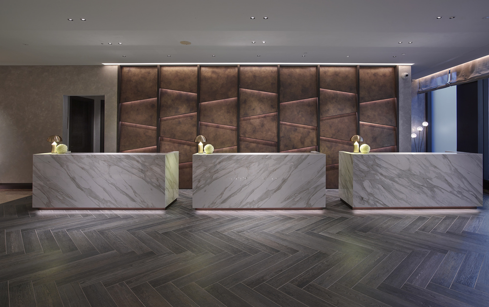 Reception Desks in Neolith Calacatta Gold bookmatch Neolith, rear panels in Oikos Bronze