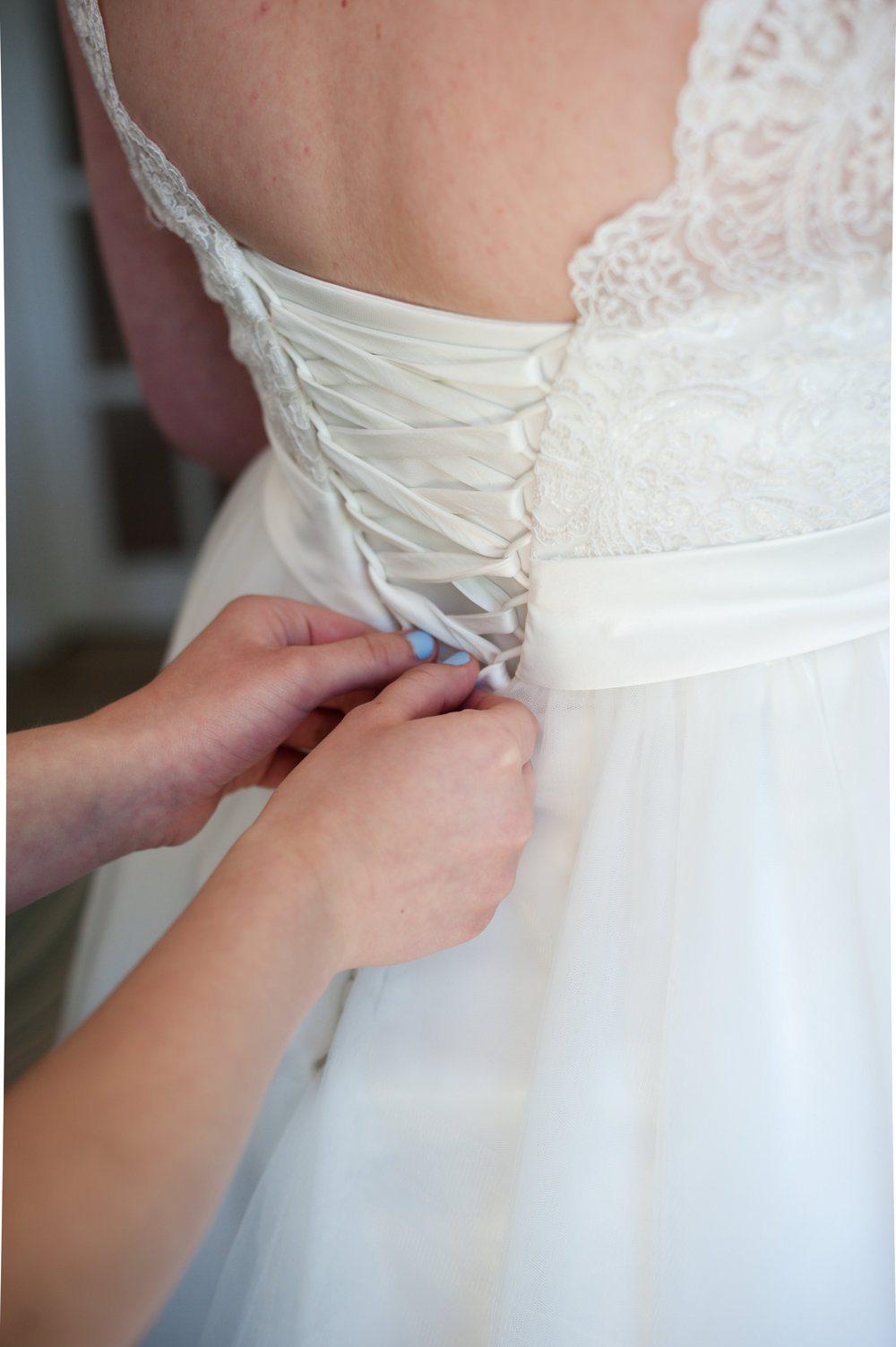 Hertfordshire Wedding Photographer - Hertford County Hall - Bridal prep - lacing up the dress - wedding dress laced