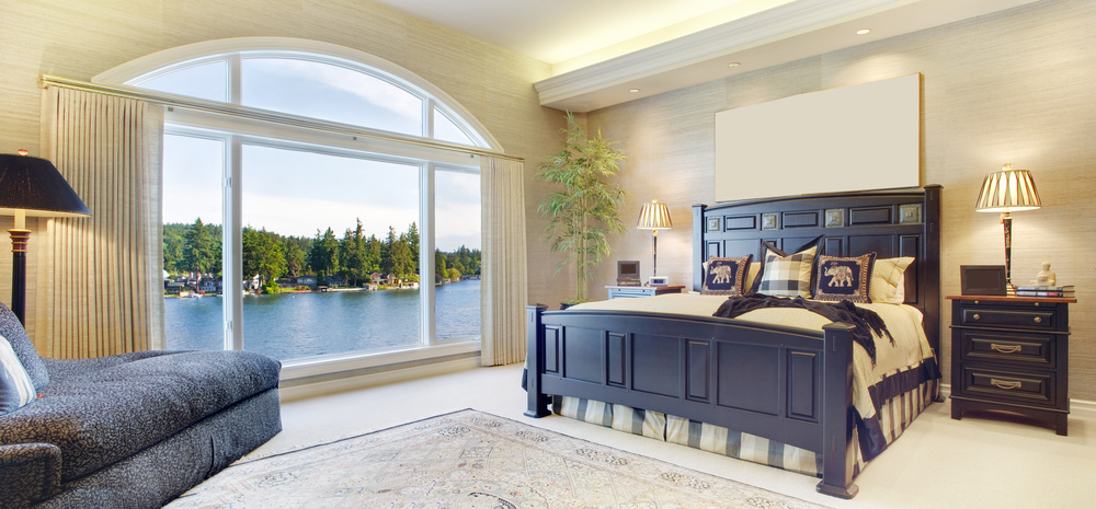 Featured here is a custom window treatment created to compliment the wonderful view within this master suite on the lake. In this classic linen look, a rippled fold panel fabric draws the eye to a clean lined presentation, showcasing this breathtaking view without obscuring it.