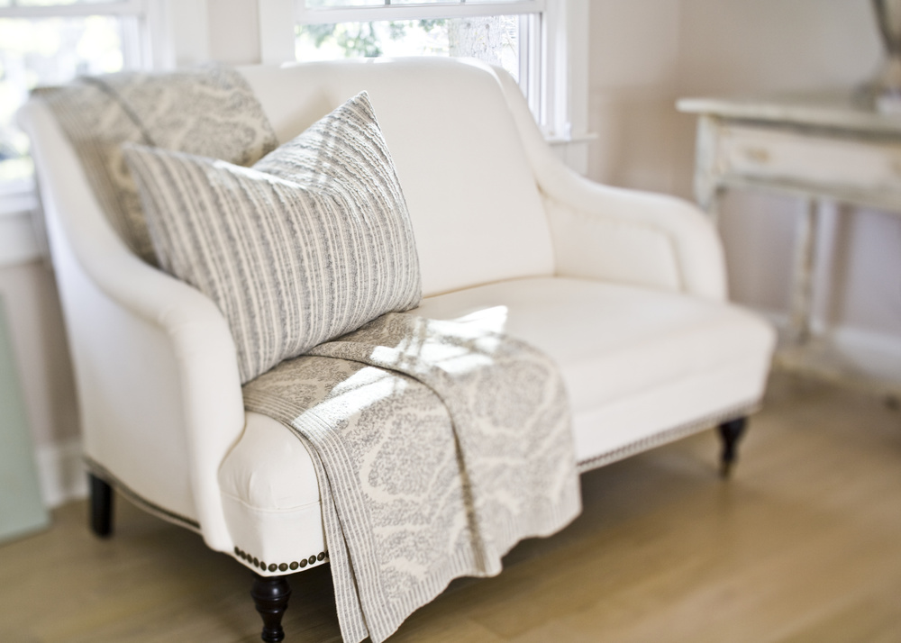 Here, an adorable small settee is placed next to an antique vanity in the same color within this master suite. The settee was refinished in an ivory cream fabric, detailed with dark nail heads and simple stained legs for added contrast. The addition of a custom upholstered pillow and chenille shawl compliment the underlying presentation.