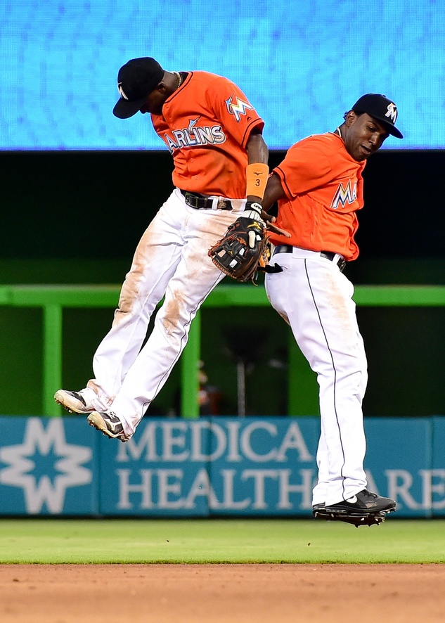 Jul 10, 2016; Miami, FL, USA; Miami Marlins shortstop Adeiny Hechavarria (left) celebrates with Marlins center fielder Marcell Ozuna (right) after defeating the Cincinnati Reds 7-3 at Marlins Park. Mandatory Credit: Steve Mitchell-USA TODAY Sports