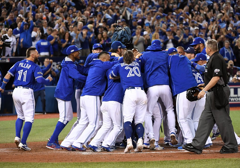 Oct 4, 2016; Toronto, Ontario, CAN; Toronto Blue Jays designated hitter Edwin Encarnacion (10) is mobbed by teammates after he hit a walk off home run to beat the Baltimore Orioles in the American League wild card playoff baseball game at Rogers Centre. Mandatory Credit: Nick Turchiaro-USA TODAY Sports